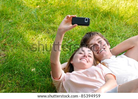 Happy couple laying on the grass make self-photo