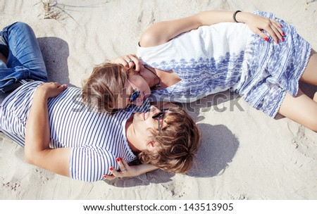 happy couple  laying together on sand