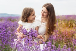 Happy couple little girl with her mother are in a lavender field holding bouquet of purple flowers