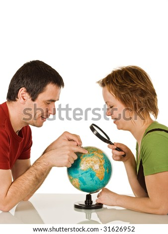 Happy couple looking at globe through a magnifying glass - isolated