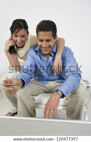 Happy couple looking at laptop while placing order through cell phone