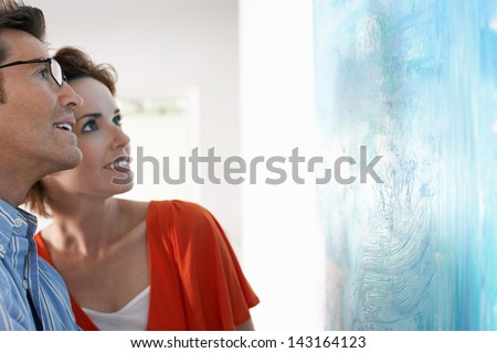Happy couple looking at modern painting in art gallery #143164123