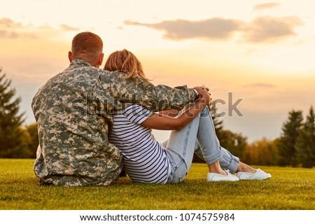 Happy couple looking at sunset. Back view, soldier and his wife sitting on the grass.