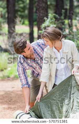 Happy couple looking face to face while tenting in forest #570751381