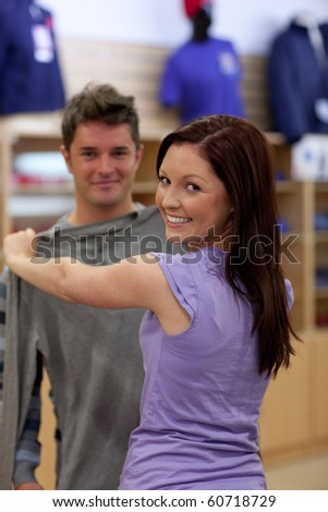 Happy couple looking for a sweat-shirt in a clothes store