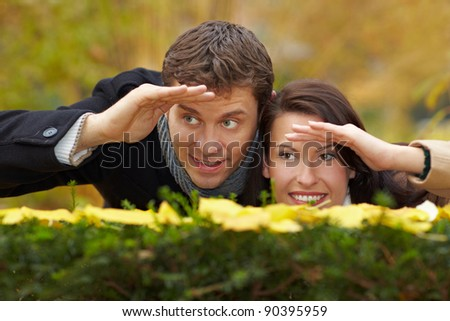 Happy couple looking over a hedge in autumn