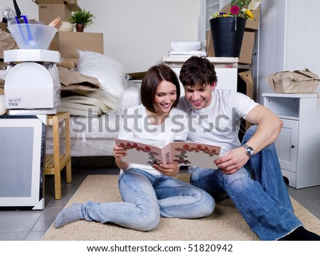 Happy couple looking through the photo album sitting on the floor together