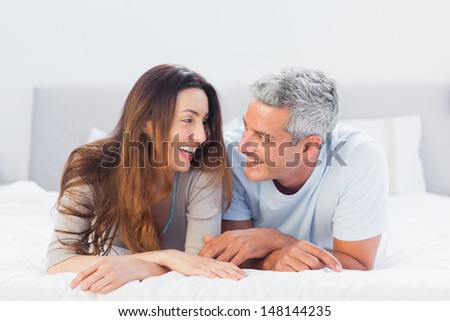 Happy couple lying on bed talking together at home