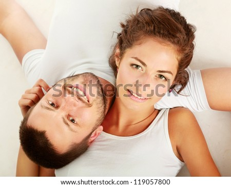 Happy couple lying on floor and smiling at camera isolated on white background
