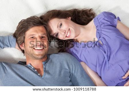 Happy couple lying on rug #1009118788