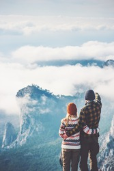 Happy Couple Man and Woman hugging enjoying mountains and clouds landscape on background Love and Travel emotions Lifestyle concept. Young family traveling active adventure vacations. rear view