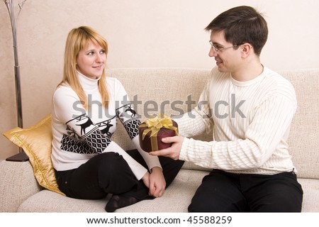 Happy couple. Man is giving gifts woman at Valentine?s day.  Male say happy birthday to female on white background.