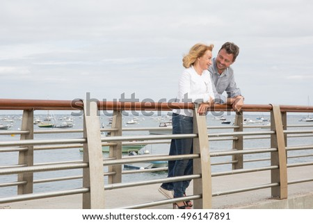 Happy couple middle aged in love on the bridge