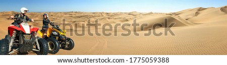 Happy couple of ATV quad bikers laughing joyful, cheerful and driving in sand dunes desert panorama. Young  couple in outdoor activity driving quadbike in Namib desert, Namibia, Africa, Walvis Bay. Stock photo ©