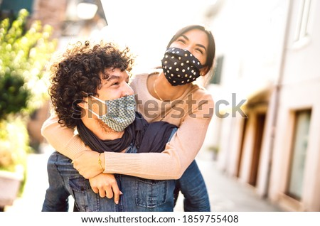 Happy couple of lovers enjoying winter travel time outdoor - Handsome guy with nice girl on piggy back moment - New normal love concept with boyfriend and girlfriend together on warm vivid filter