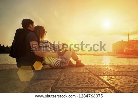 Happy couple of lovers relaxing on the sea pier under sunset sun light at evening time.