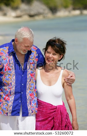 Happy couple of senior having a walk by the edge of the sea