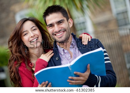 Happy couple of students with a notebook and smiling outdoors