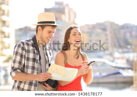 Happy couple of tourists enjoying vacation travel  holding smart phone and touristic guide #1438178177