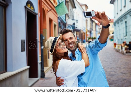Happy couple of tourists taking selfie in old city