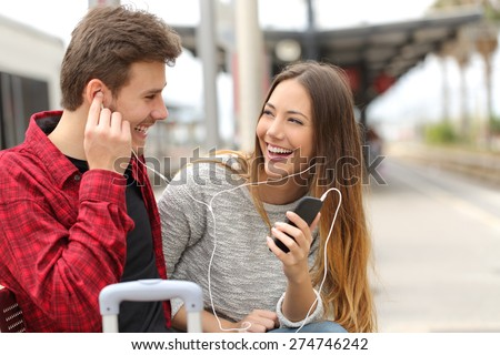 Happy couple of travelers sharing music on holidays during a travel in a train station #274746242