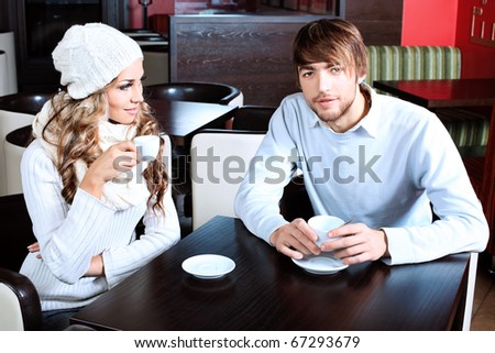 Happy couple of young people having a date at a caf