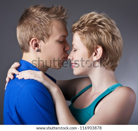 Happy couple of young people having fun together against black background