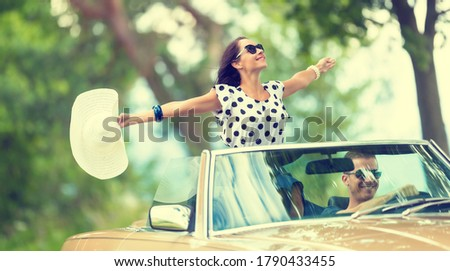 Happy couple on a summer roadtrip with girl sitting on top of a convertible back seat, arms open, hat in her hand. stock photo