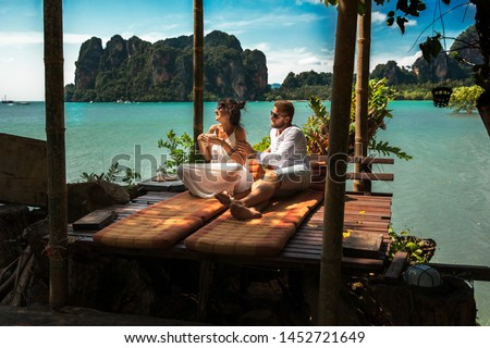 Happy couple on an island off the coast.  Young couple by the sea. The couple travel around the world. Couple in love at the lagoon. Honeymoon trip. Relax on the island. Lovers relax on the sea