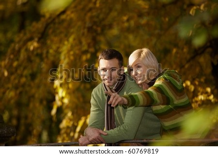 Happy couple on autumn walk in park, woman showing something to man, smiling.?