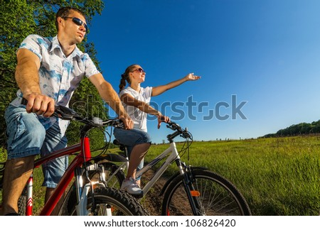 Happy couple on bikes looks into the distance while enjoying the outdoors