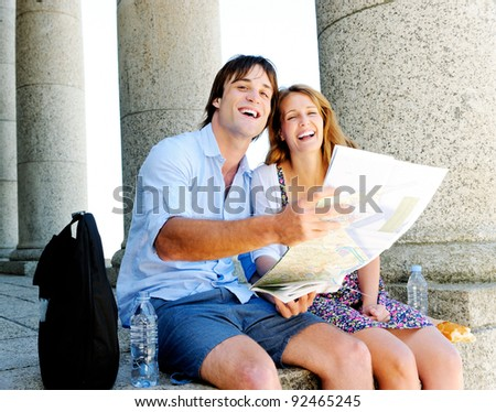Happy couple on holiday, holding a map