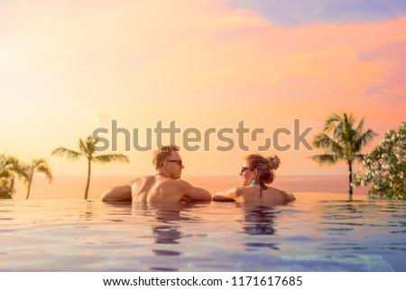 Happy couple on honeymoon in luxury hotel pool