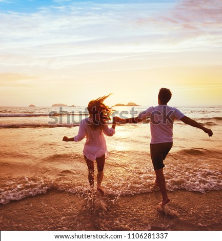 happy couple on honeymoon vacation travel, romantic getaway dream beach holidays, happiness, silhouettes of man and woman running to the sea at sunset together