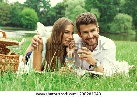 Happy couple on picnic drinking white wine