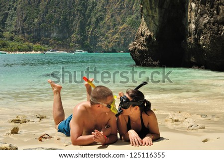 Happy couple on the beach dressed in snorkelling.