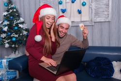 Happy couple, on the eve of the new year, doing online shopping sitting on the couch at home.
