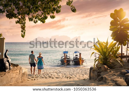 Happy couple on the tropical beach of Phi Phi island at sunset in Southern Thailand. Travel magazine concept.