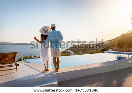 Happy couple on vacation time enjoys the summer sunset by the pool with an aperitif drink Foto stock ©
