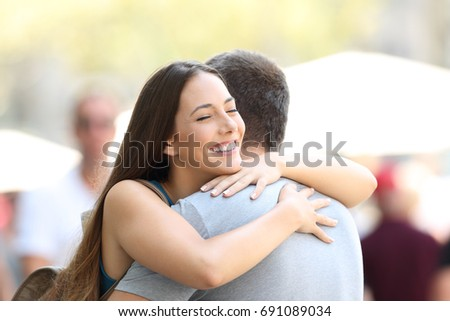 Happy couple or friends hugging on the street after encounter