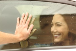 Happy couple or friends saying good bye touching hands through a car window before travel