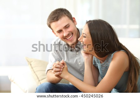 Happy couple or marriage looking each other laughing and holding hands sitting on a sofa at home #450245026