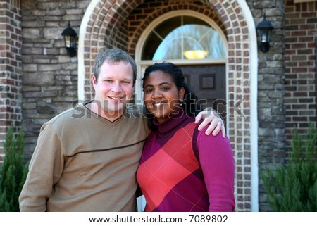 Happy couple outside in front of their new house