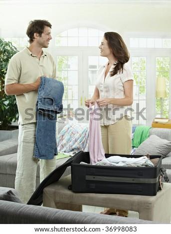 Happy couple packing clothes into suitcase, preparing for vacation.