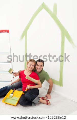 Happy couple painting in their home - sitting with utensils