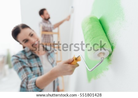 Shutterstock Happy couple painting walls in their new house: the man is standing on a ladder and the woman is using a paint roller and applying bright green paint