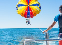 Happy couple Parasailing in Dominicana beach in summer. Couple under parachute hanging mid air. Having fun. Tropical Paradise. Positive human emotions, feelings, family, children, travel, vacation.