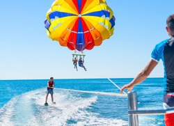 Happy couple Parasailing in Dubai beach in summer. Three people rest on the sea. Parachute and water skiing.