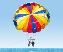 Happy couple Parasailing in Turkey beach in summer. Couple under parachute hanging mid air. Having fun. Tropical Paradise. Positive human emotions, feelings, family, children, travel, vacation.