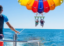 Happy couple Parasailing near Miami Beach in summer. Couple under parachute hanging mid air. Having fun. Tropical Paradise. Positive human emotions, feelings, family, travel, vacation.